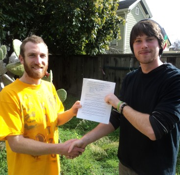 Luke Kinney holding his record agreement with Erik Lehmer, owner of Rest Easy Records
